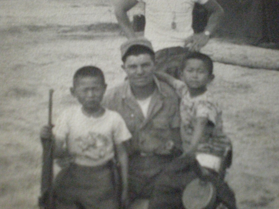 Showing his rifle to two Korean children